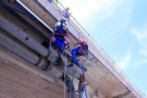 Tecnici-acrobati in azione, a Sant'Antioco, per sostituire la condotta idrica sotto il ponte.