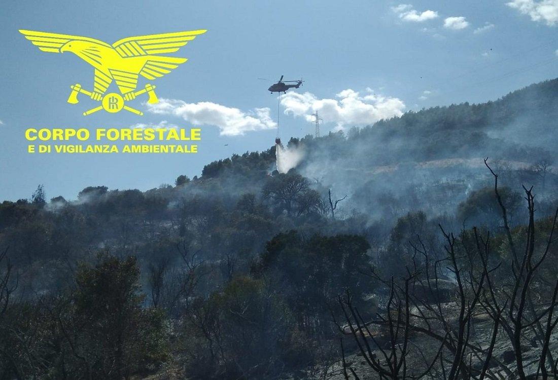 Un elicottero del Corpo forestale sta operando per bloccare le riaccensioni dovute al vento sull'incendio di ieri sera nelle campagne di Pula.
