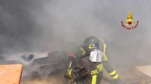 In fiamme un'auto in sosta all'interno di un parcheggio privato, a Elmas, i vigili del fuoco spengono le fiamme e mettono in sicurezza l'area